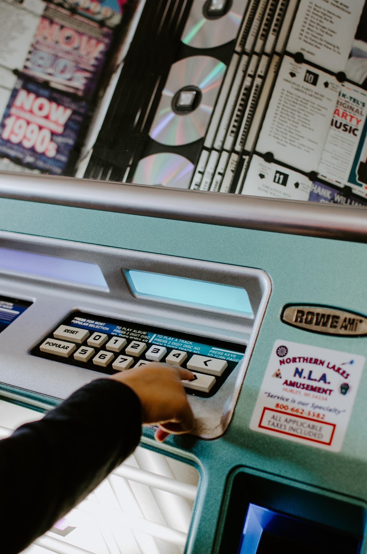 person touching white button on machine