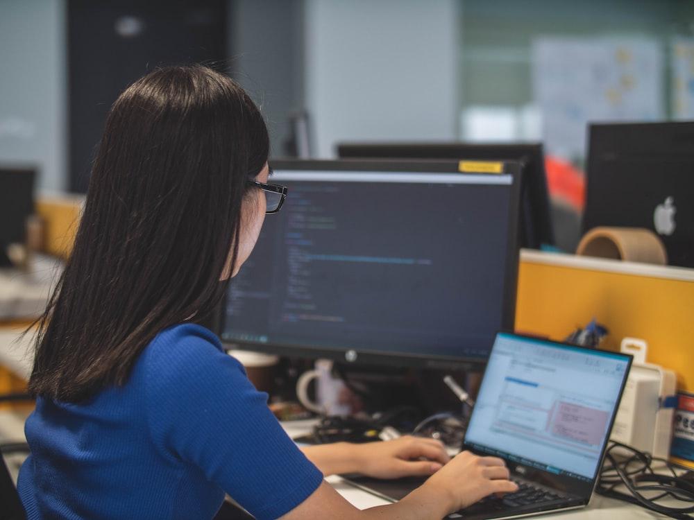 woman using black laptop computer near turned on flat screen computer monitor