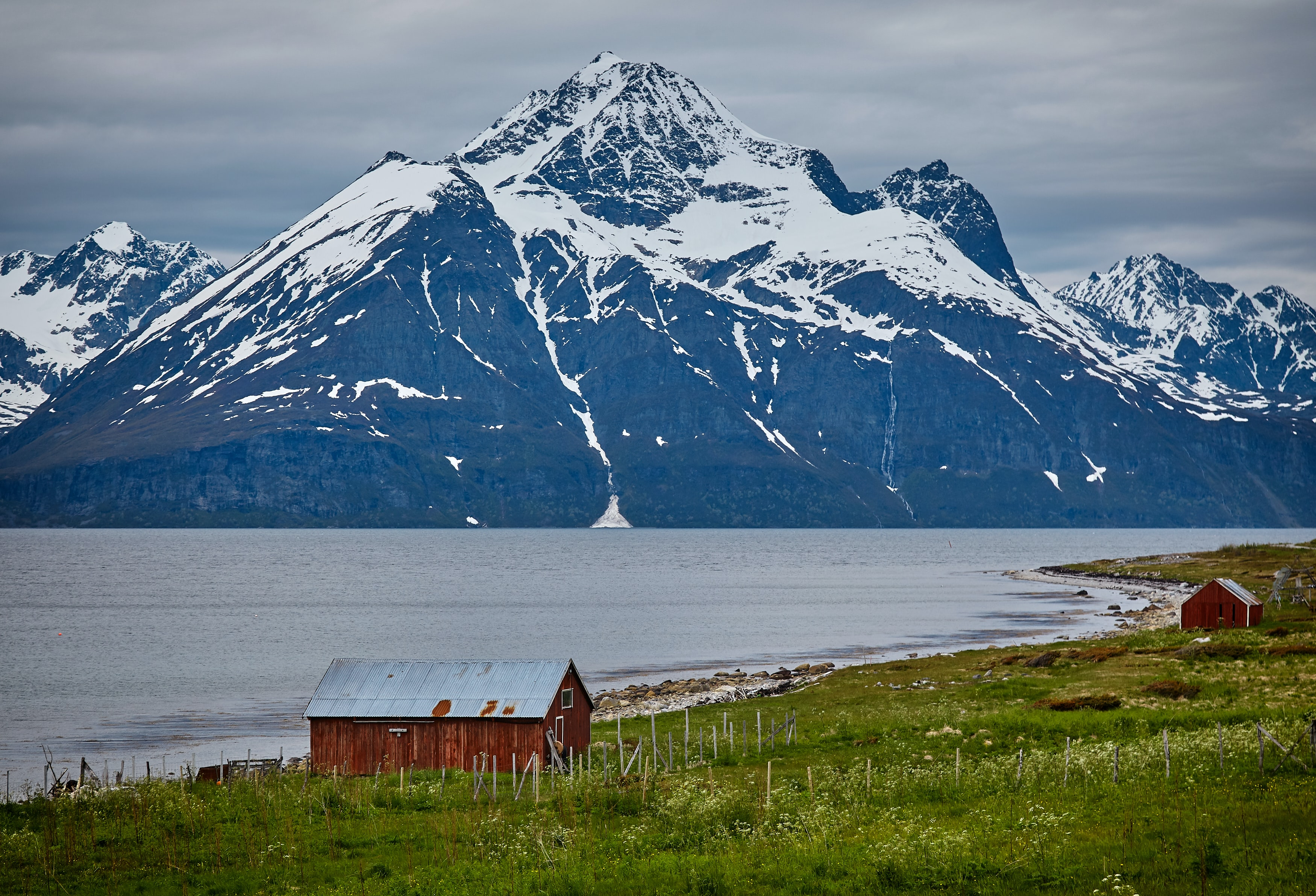 photo of two brown wooden barns near blue body of water and snow covered mountains at daytime