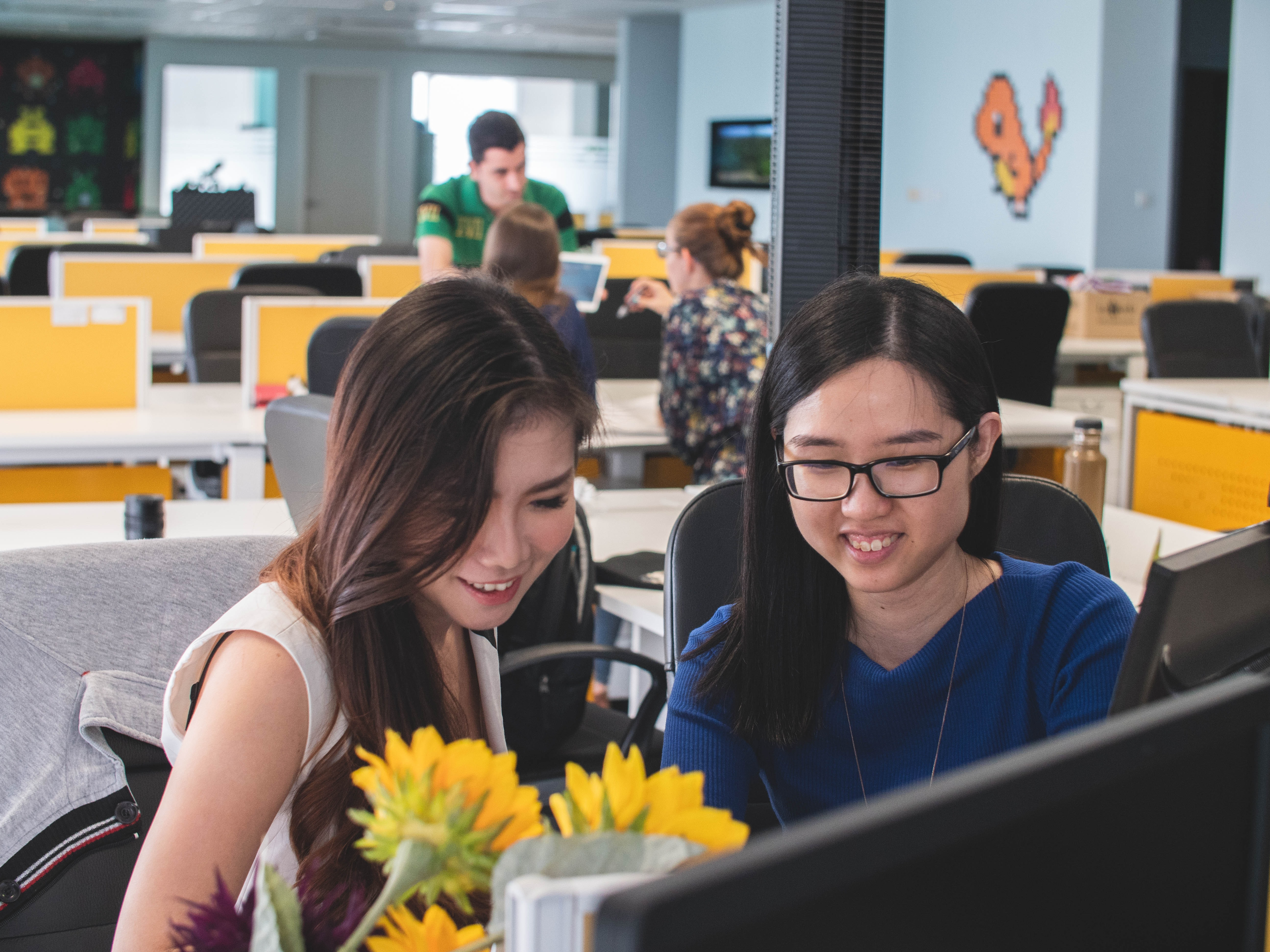 selective focus photography of two women in front of computer monitor