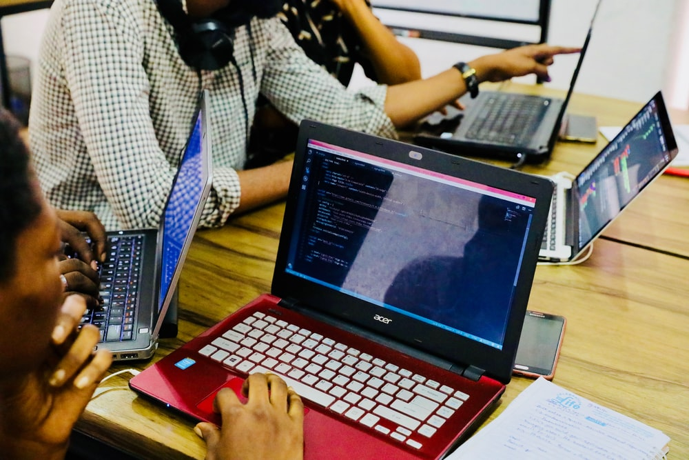 person using black and red Acer laptop computer on table