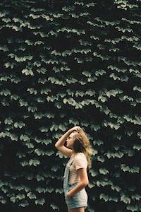 girl standing beside tree holding her hair