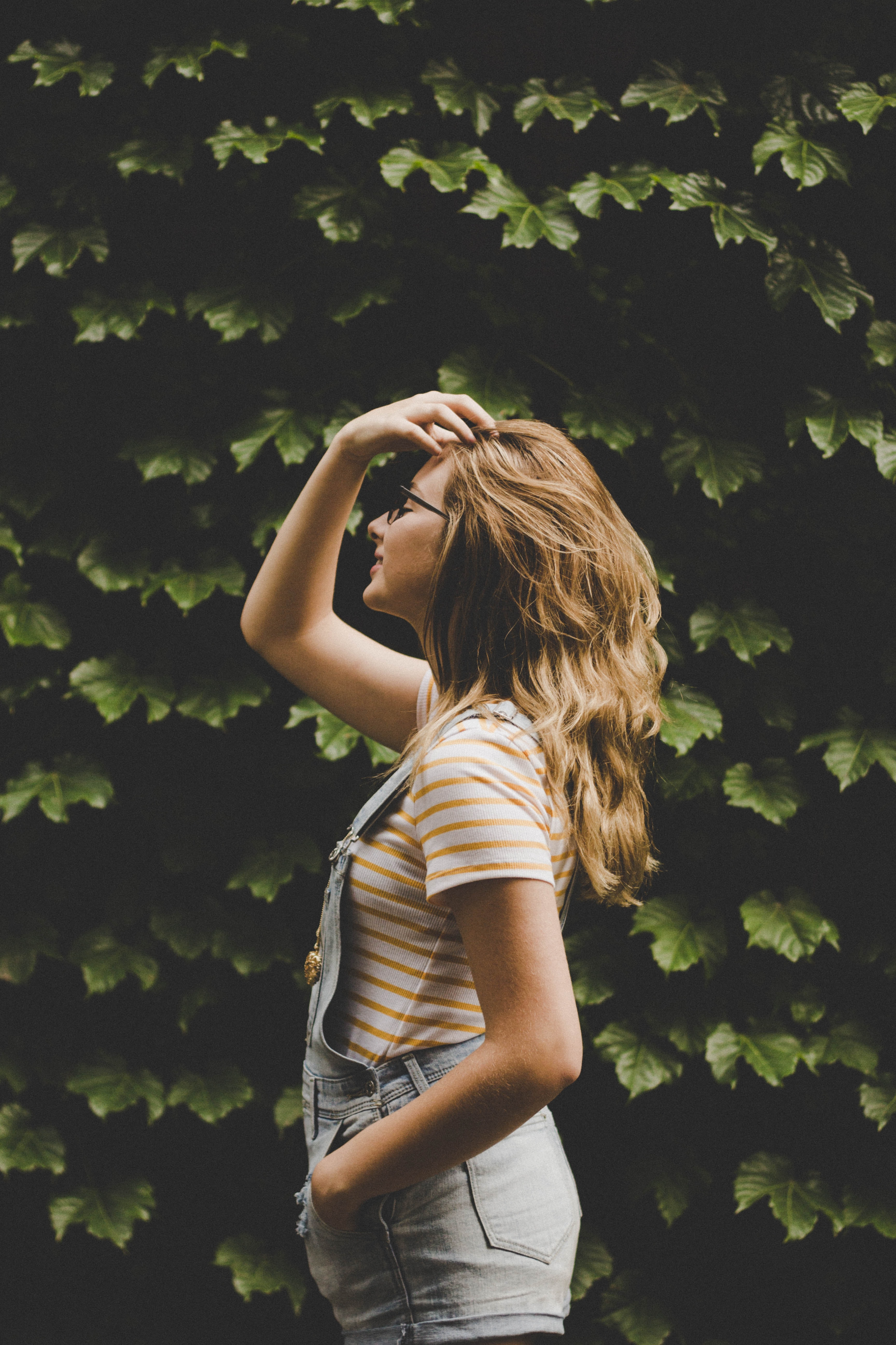 shallow focus photography of woman standing in front of plants facing sideways