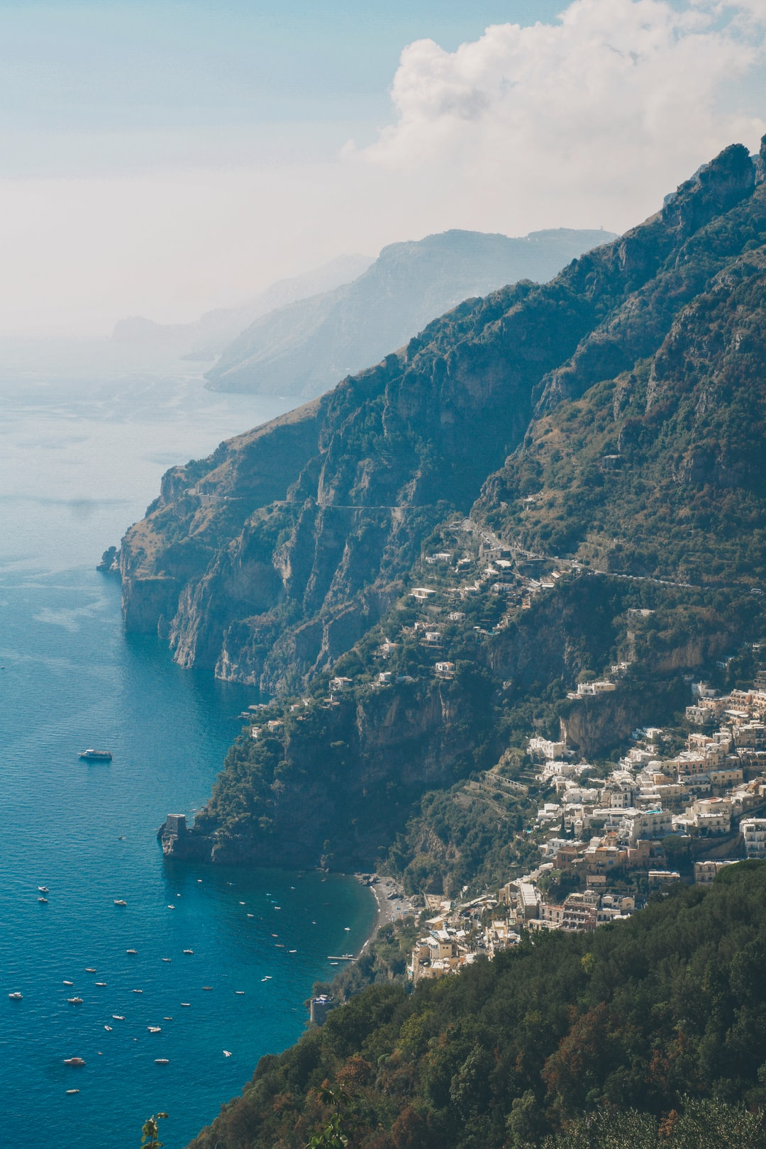 buildings and houses on top of mountains surrounded by body of water in Positano Italy