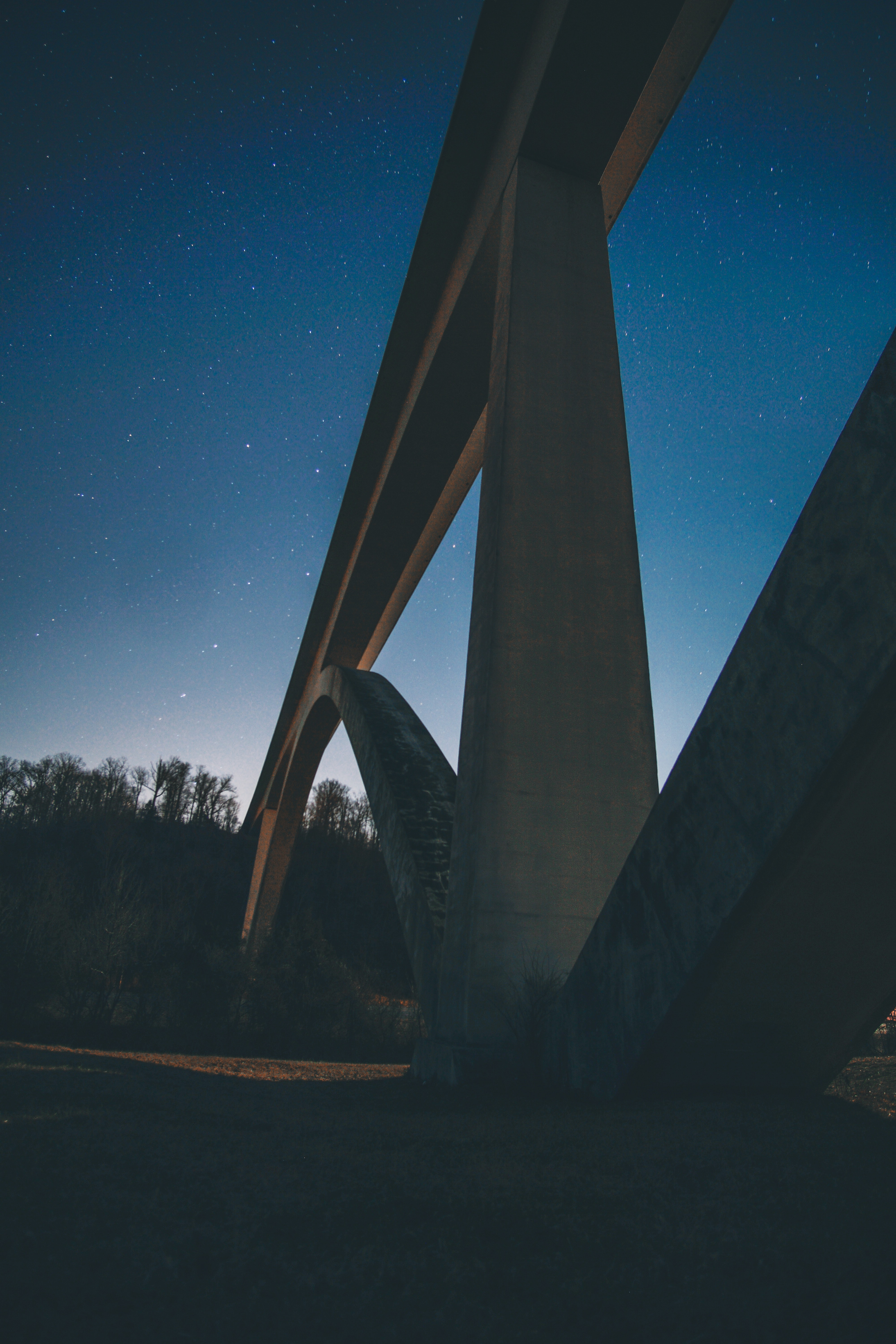 close-up photography of concrete suspension bridge during nighttime