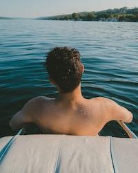 man half bath in body of water