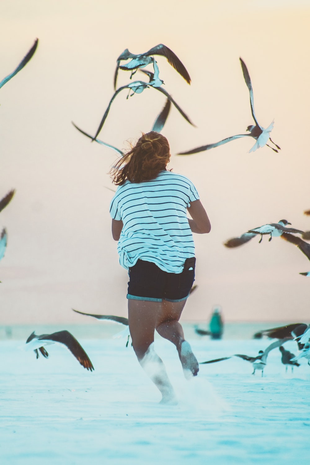 running woman surrounded by birds at daytime