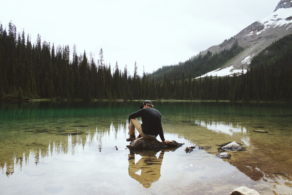 man wearing sweater sitting on stone by calm lake with trees on shore fronting snow capped mountain at daytime