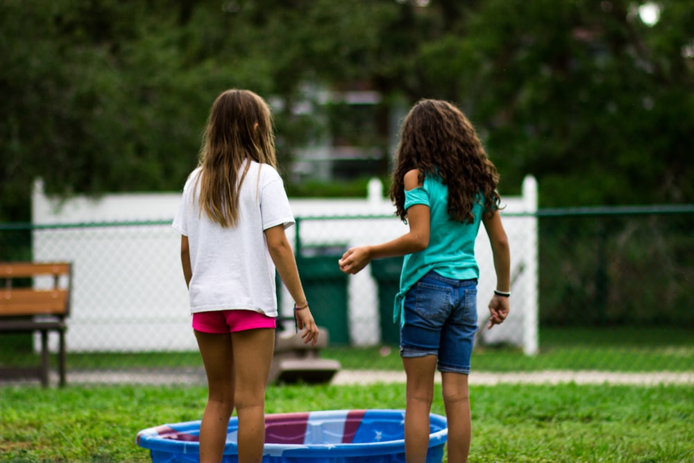two girls near round blue plastic basin