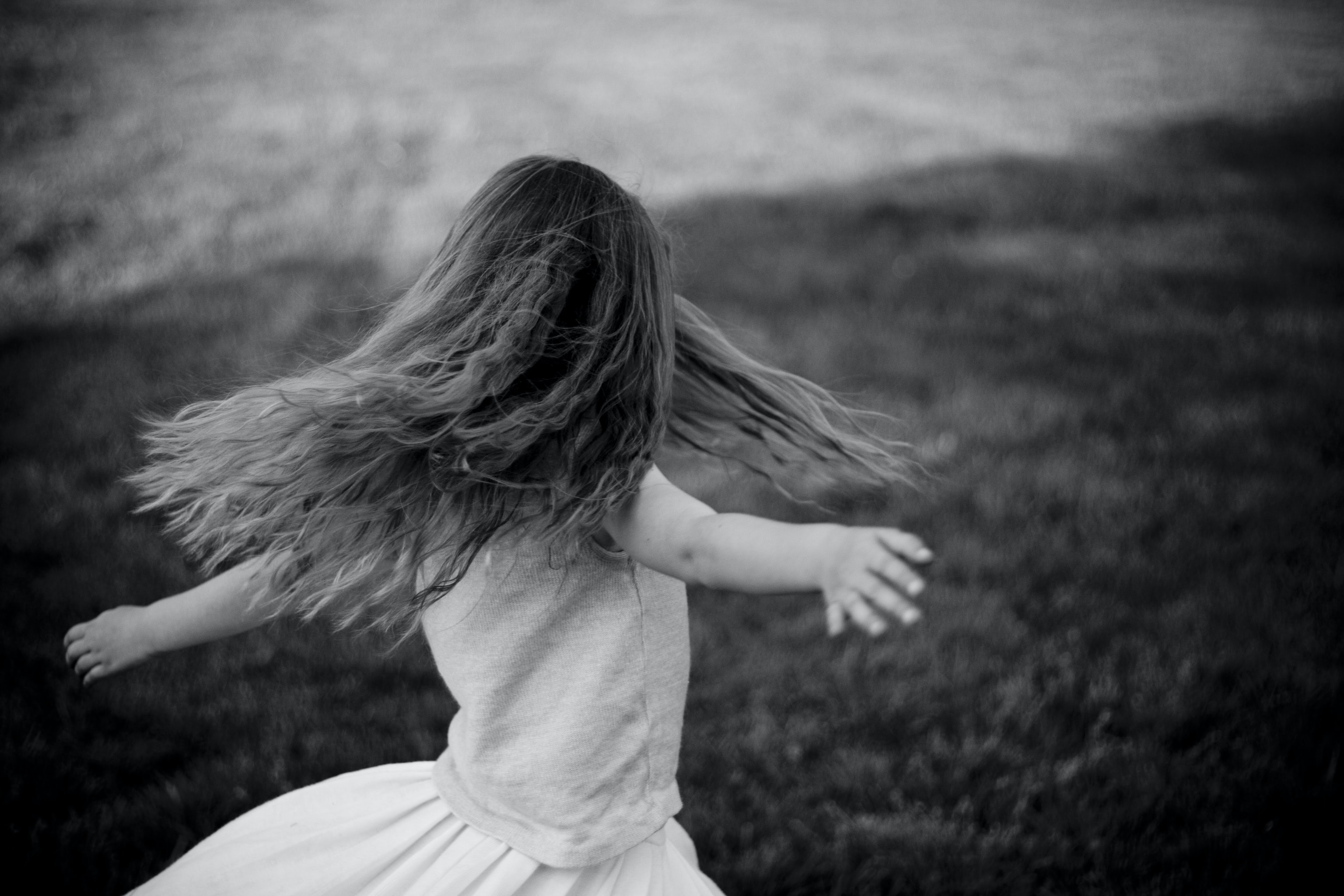 grascale photo of a girl near grass