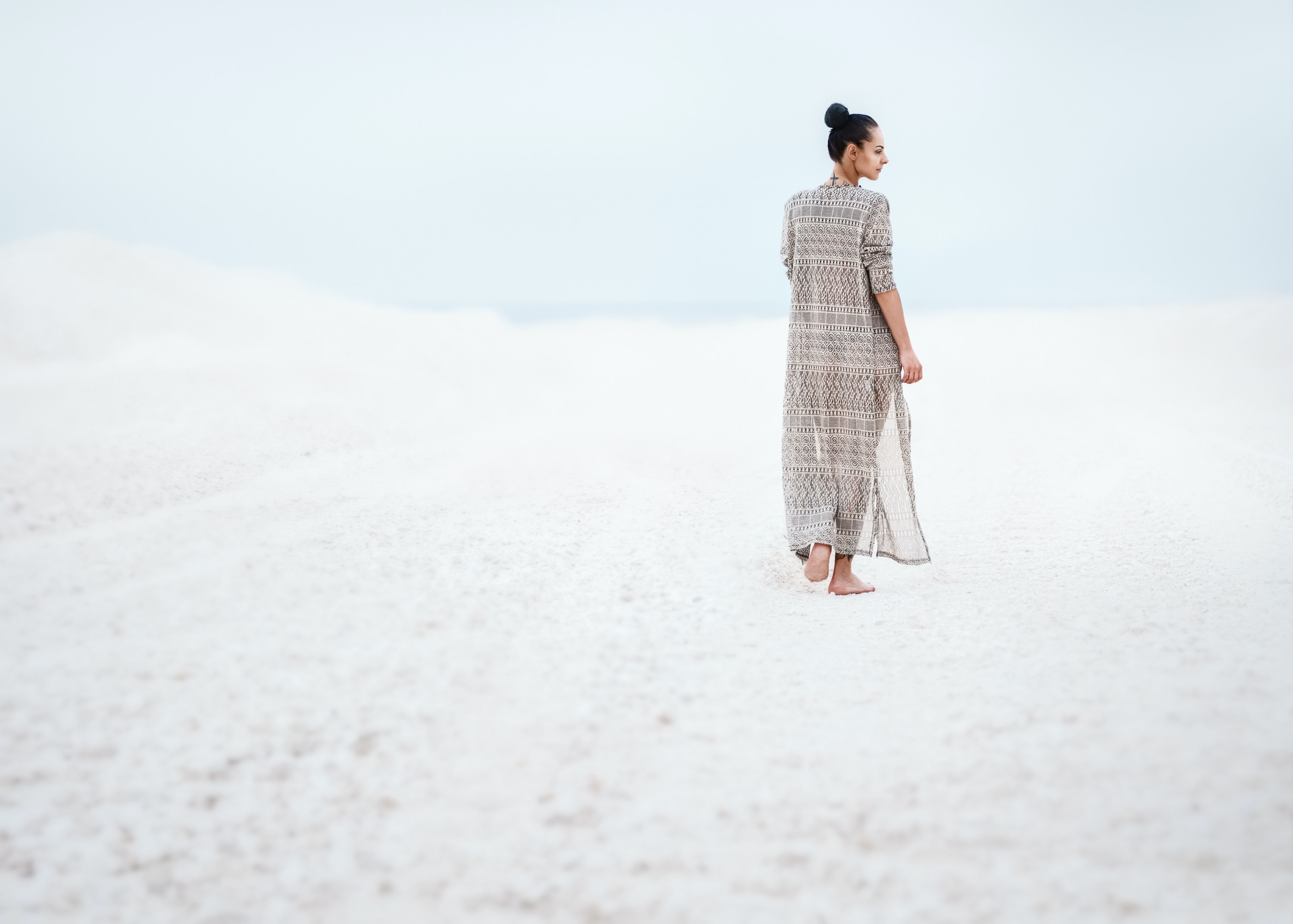 woman in gray dress walking on sand