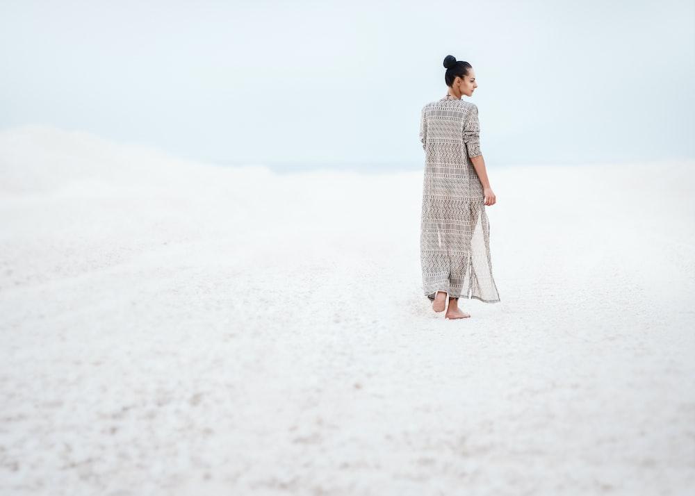 woman in gray dress walking on sand