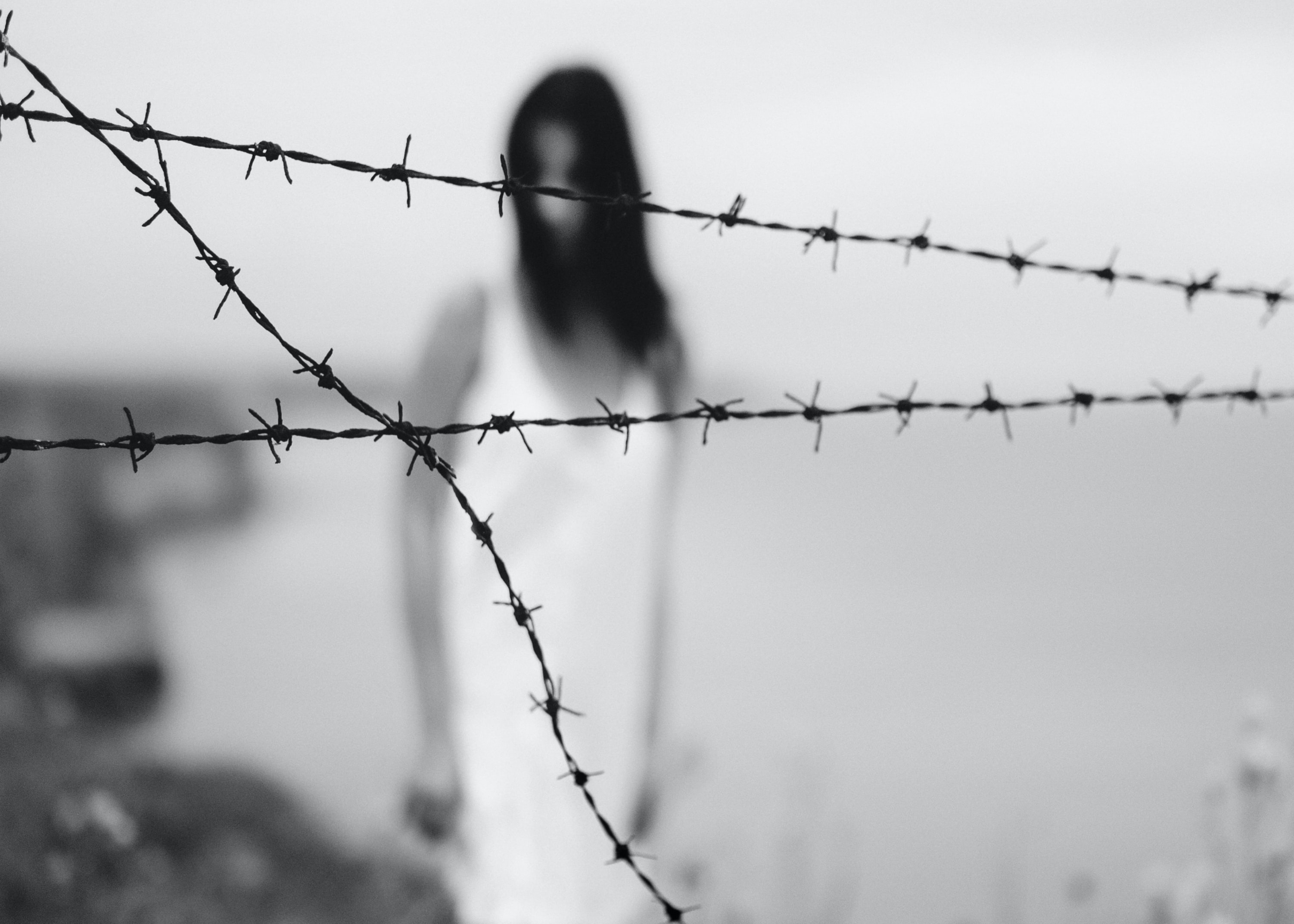 woman standing on shore near barbed wire fence