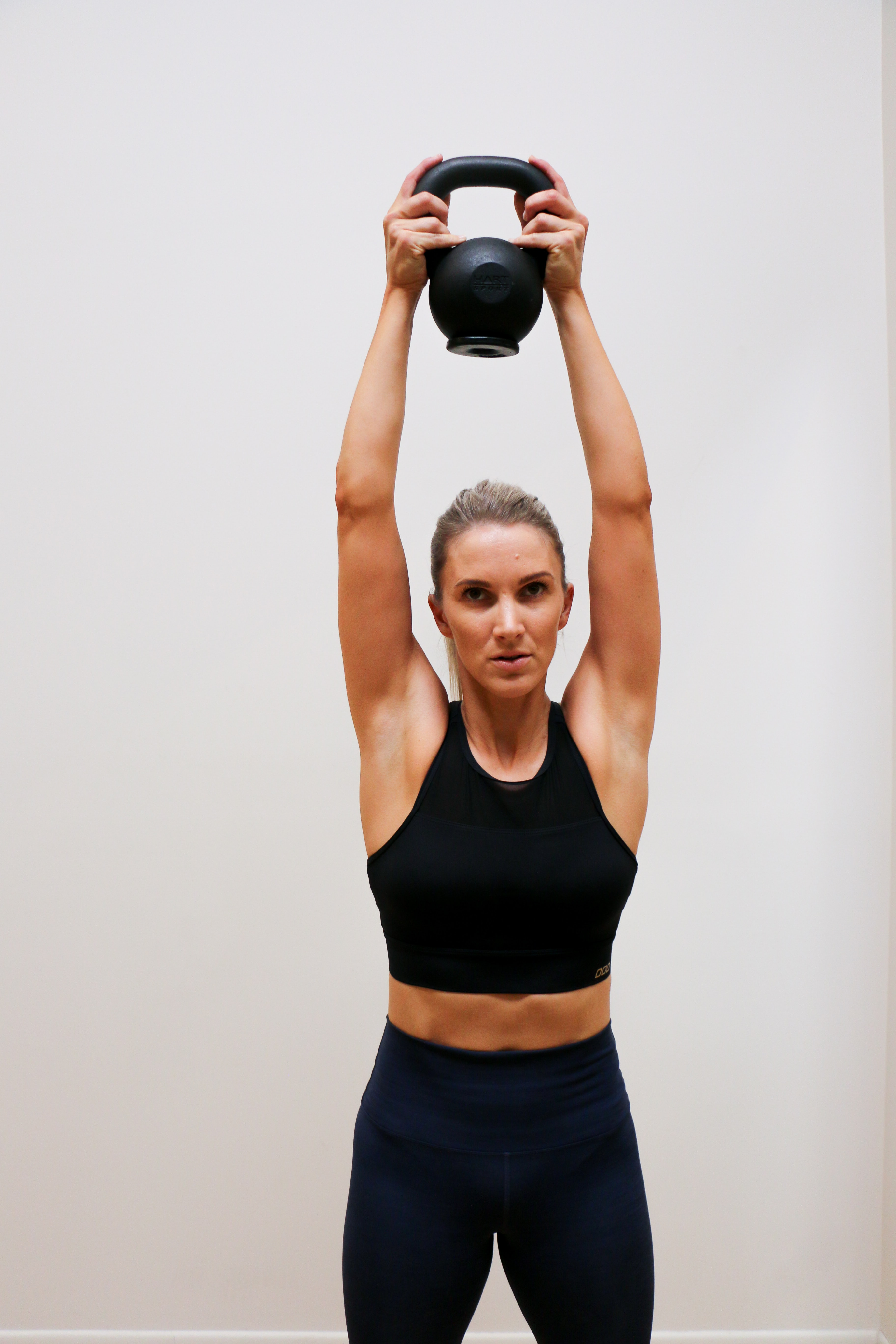woman holding kettle bell above her head