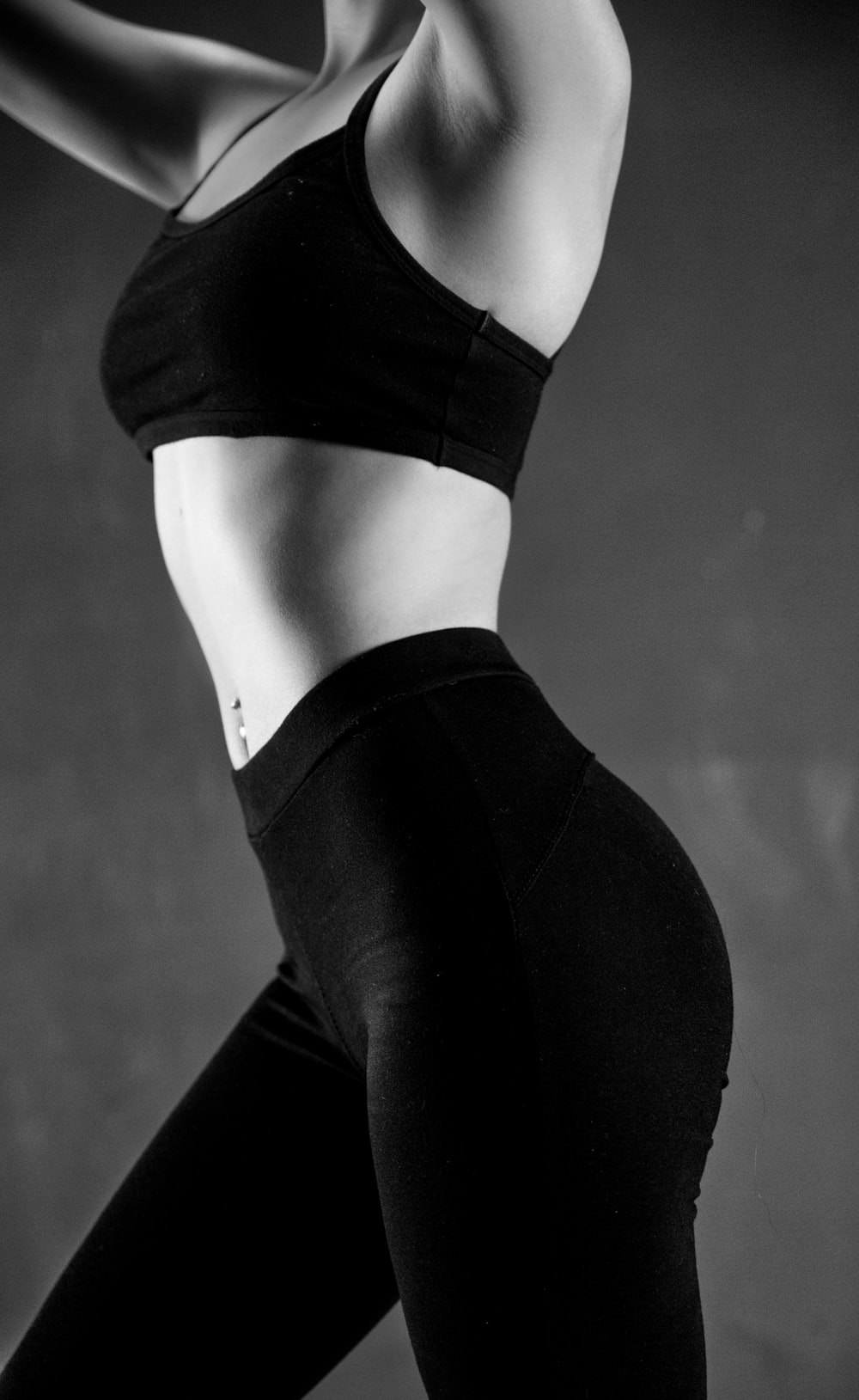 grayscale photo of person wearing sports bra and leggings