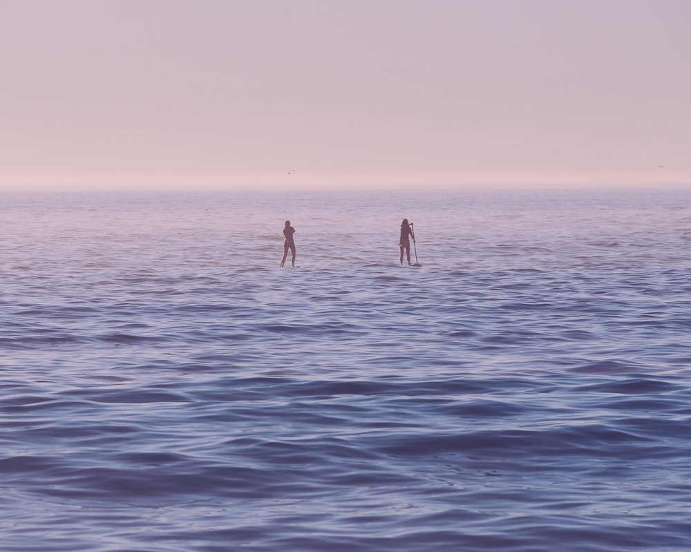 two person standing on surfboard on sea at sunrise