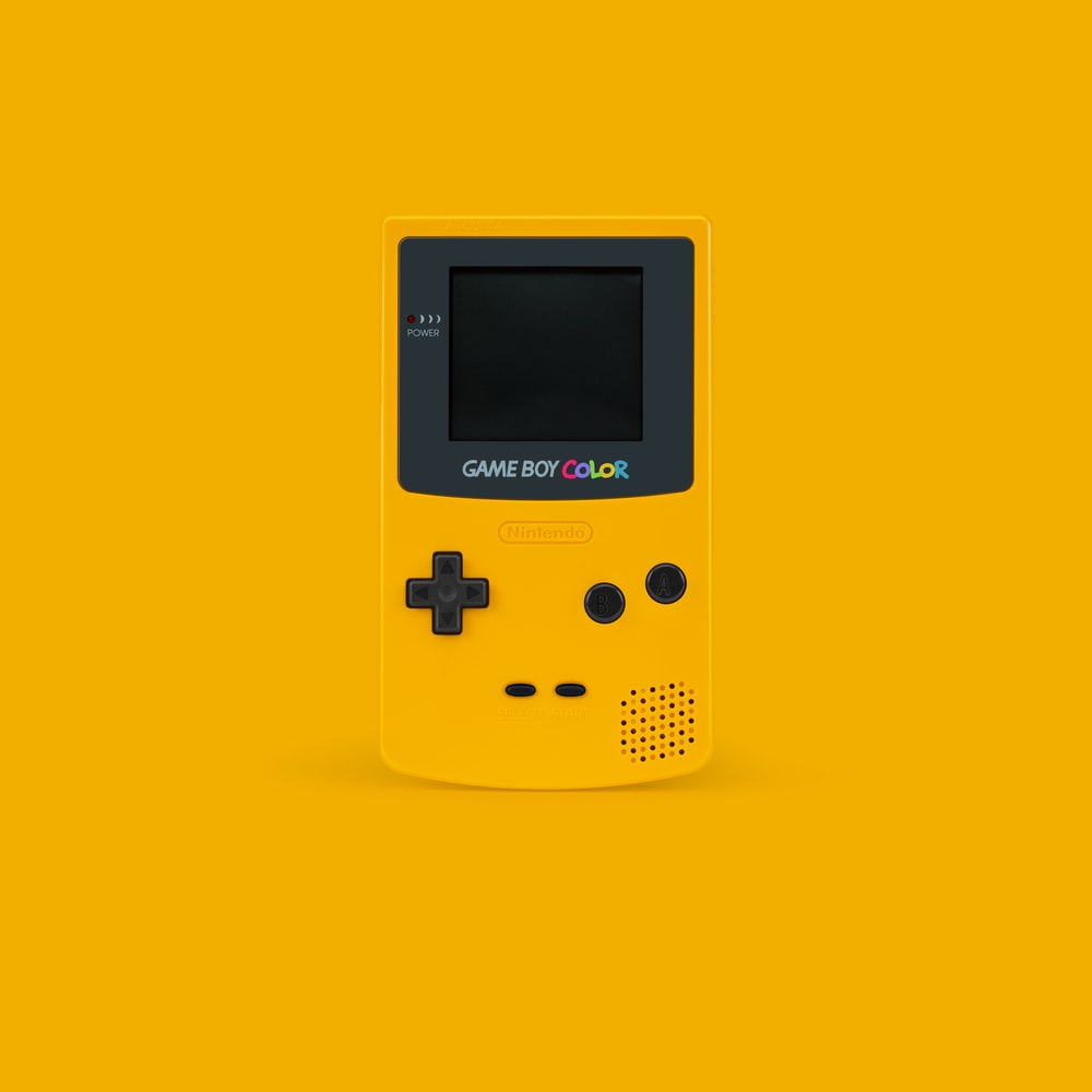 white and black Nintendo Game Boy Color on yellow surface