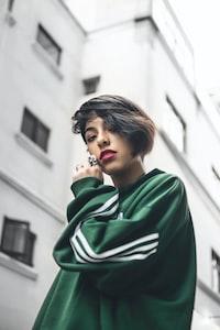 woman wearing green jacket near white high-rise building