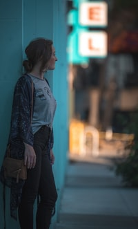woman wearing gray denim jeans standing beside teal painted wall looking at tree selective focus photography