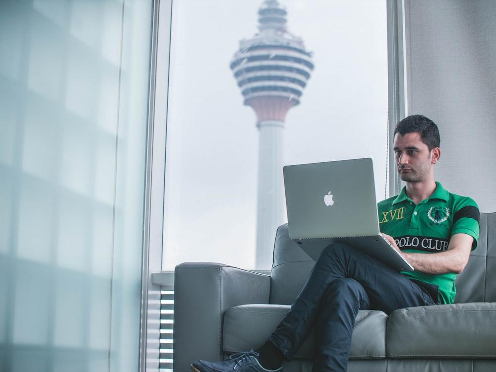 man sitting on sofa holding MacBook