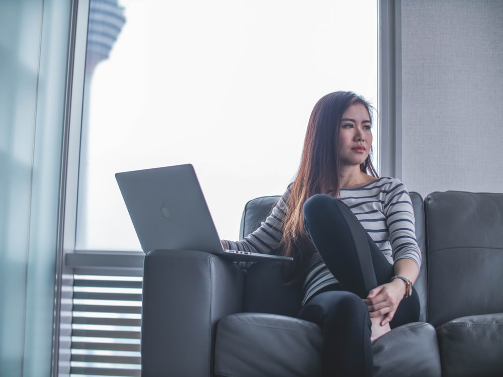 woman sitting on couch while using laptop computer