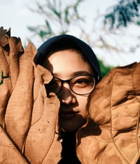 person hiding in brown leafed decors