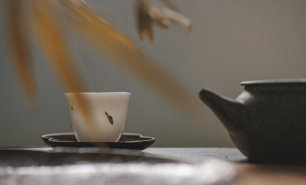 white tea cup on black saucer near black tea pot