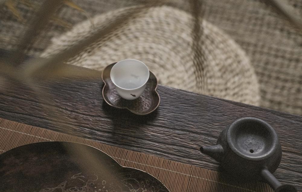 white teacup on saucer near teapot
