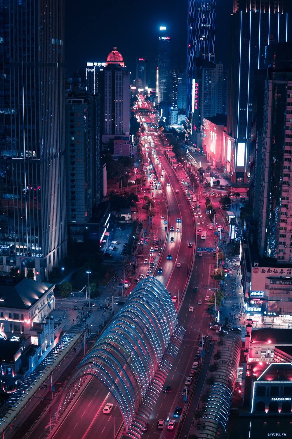 time lapse photography of vehicle traveling near road between high-rise building during nighttime