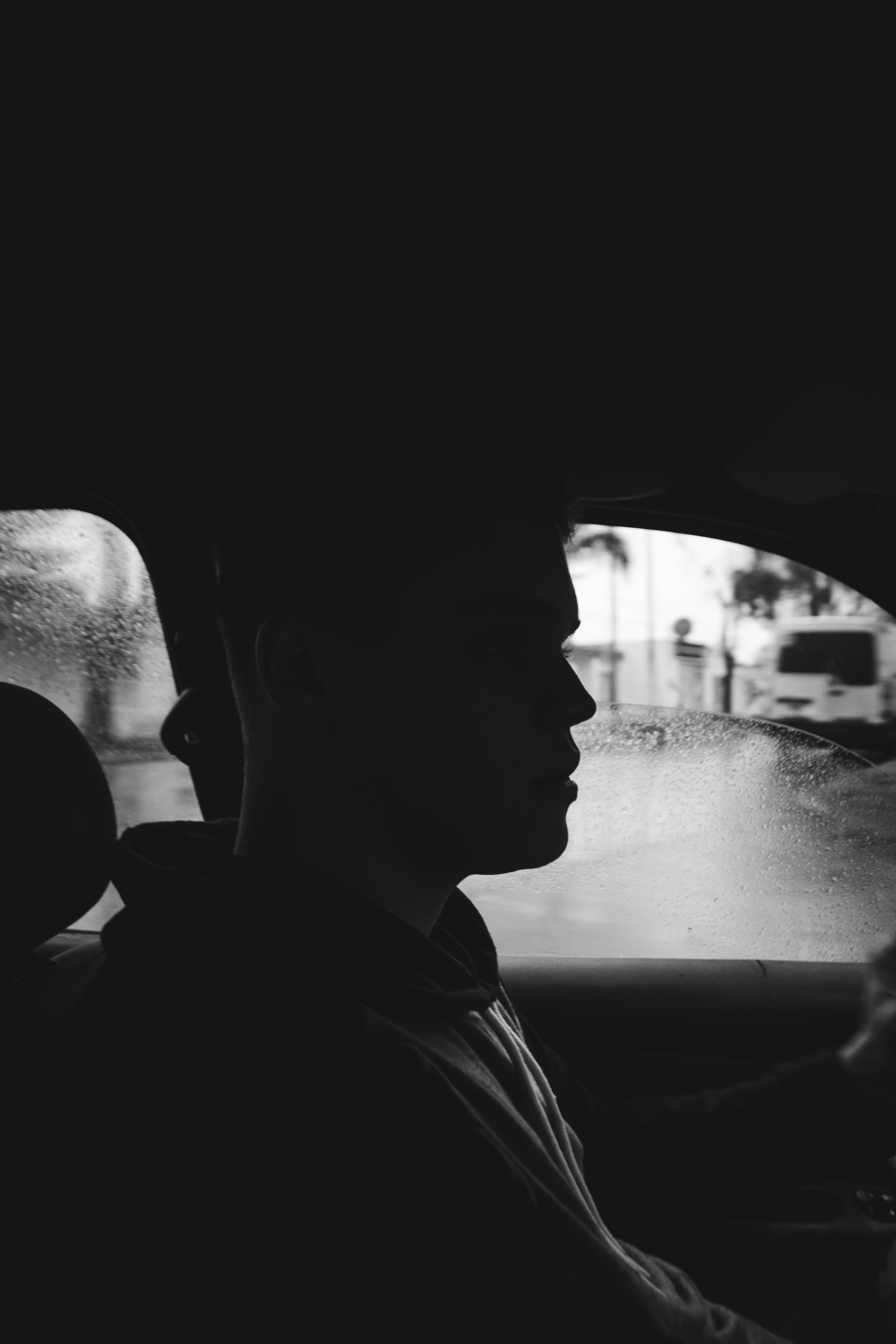 grayscale photography of man inside car