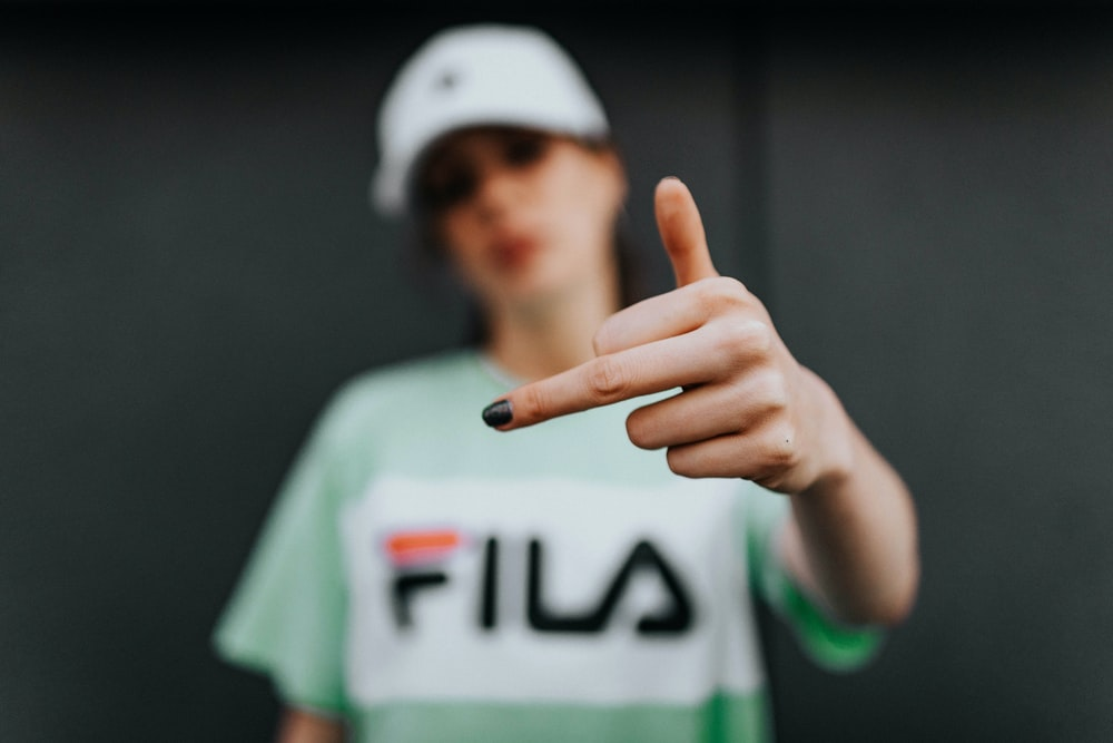 selective focus photo of woman raising middle finger