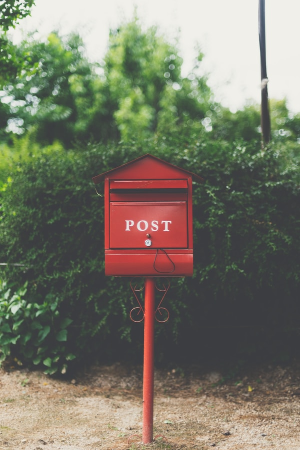 red wooden mailbox near green leaf plant