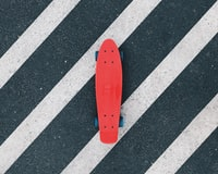 red cruiserboard on gray and white pedestrian lane