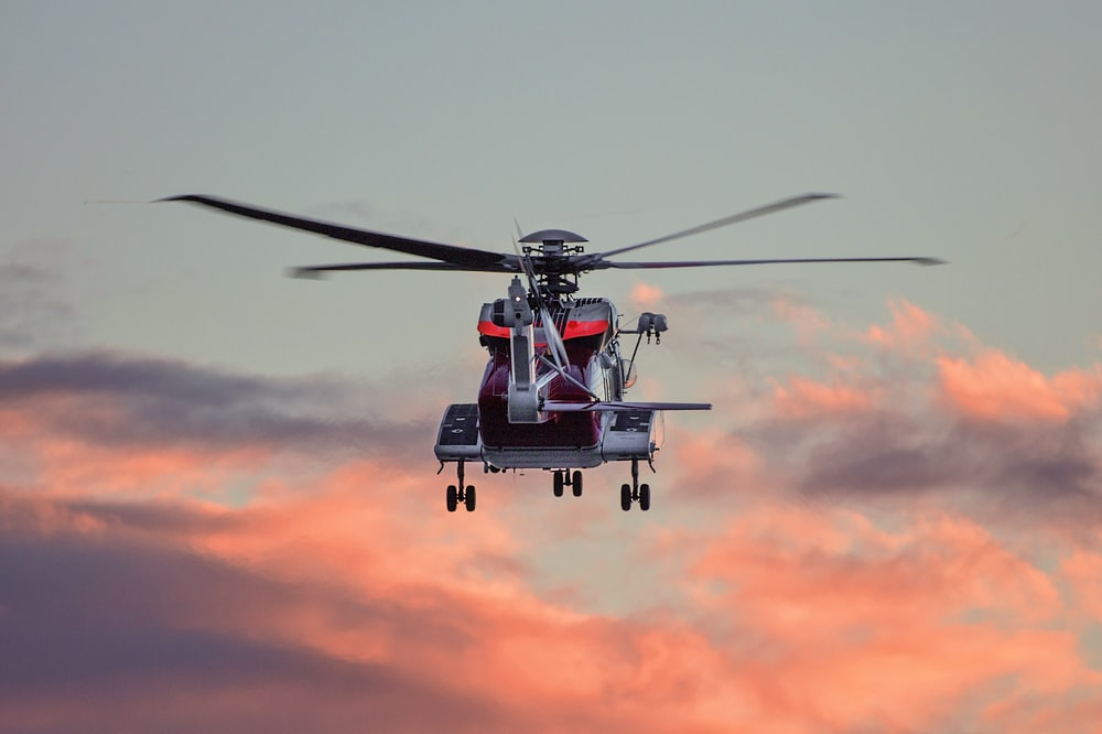 red and white hovering helicopter in mid-air photography