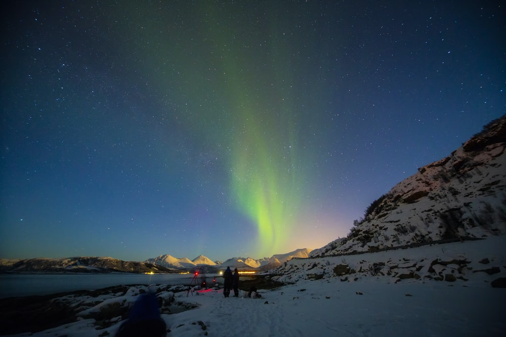two people standing under aurora lights