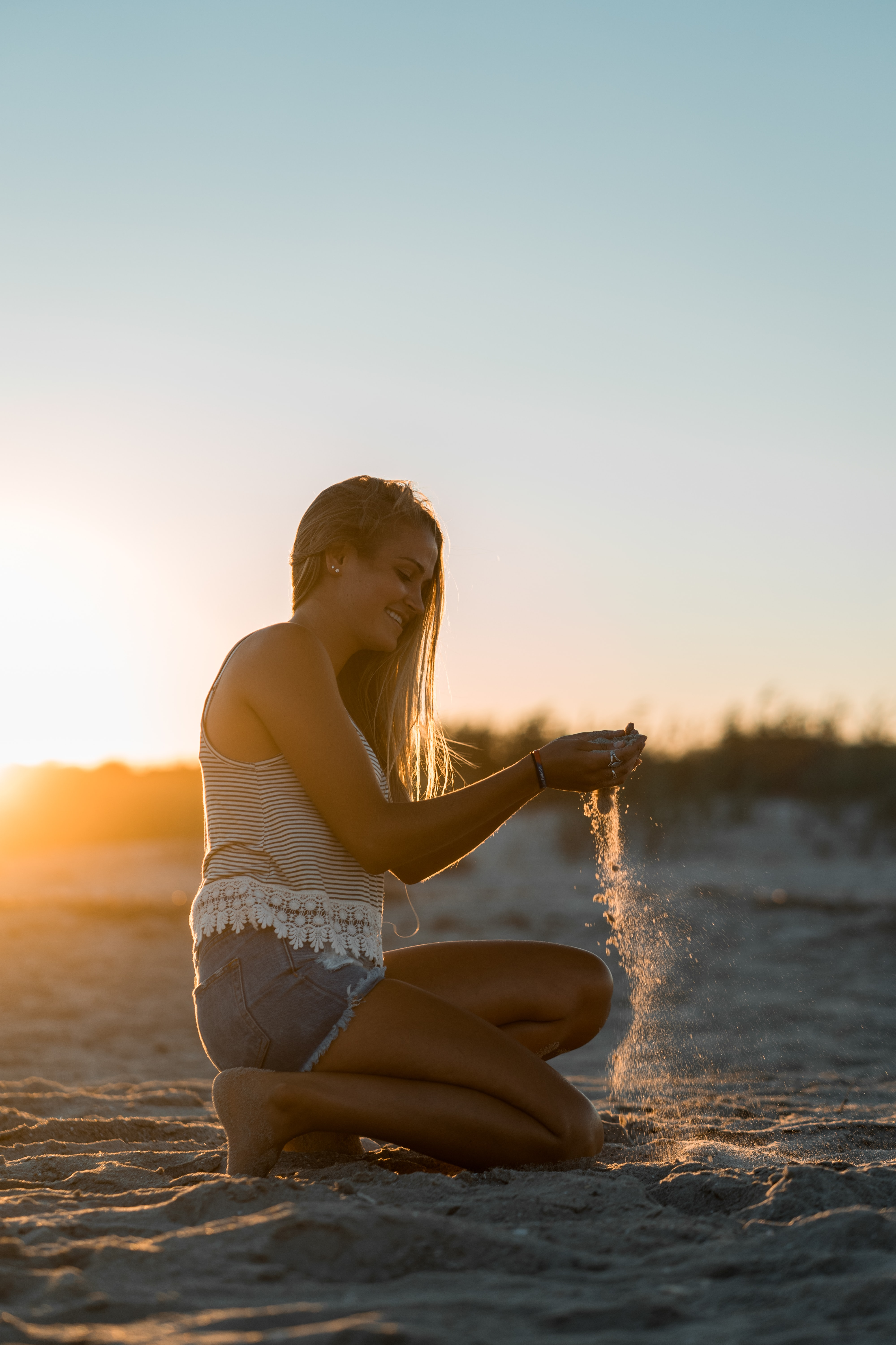 woman playing with sand during sunset