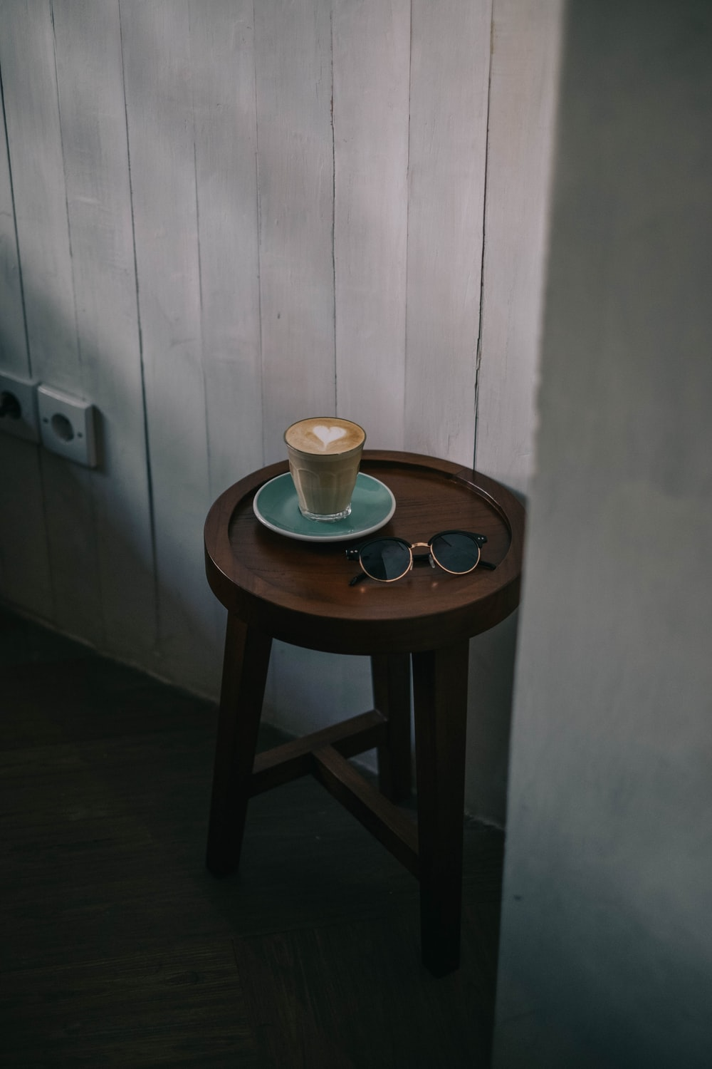coffee latte with heart art on brown wooden end table beside black sunglasses