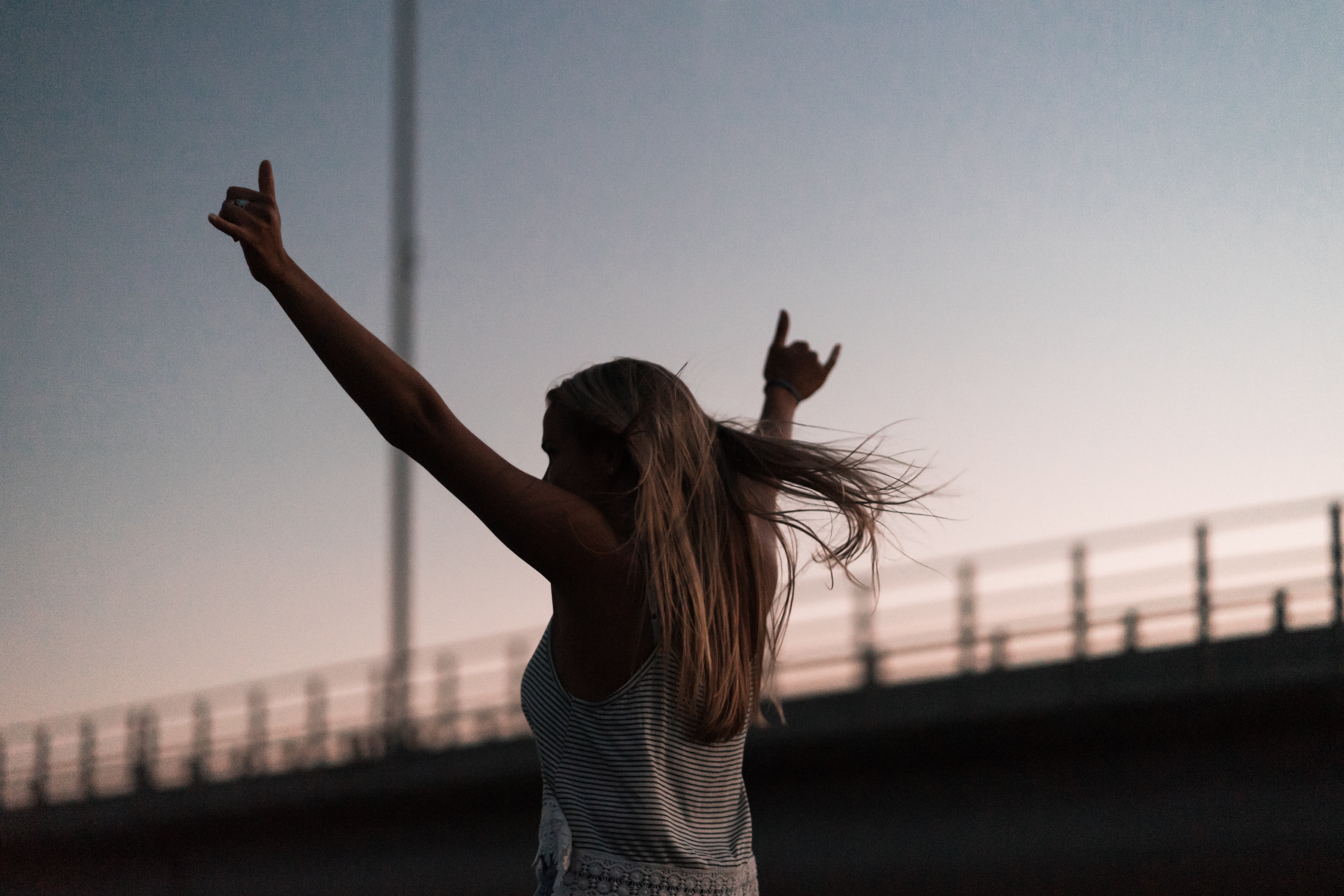woman raising his hands during daytime