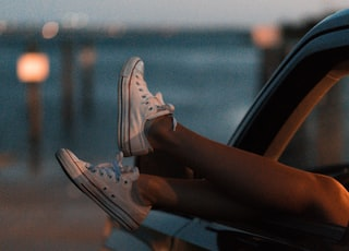 selective focus photography of person wearing white low-top sneakers inside vehicle