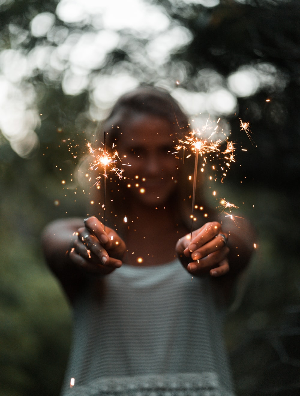 selective focus photography of woman holding two sparklers