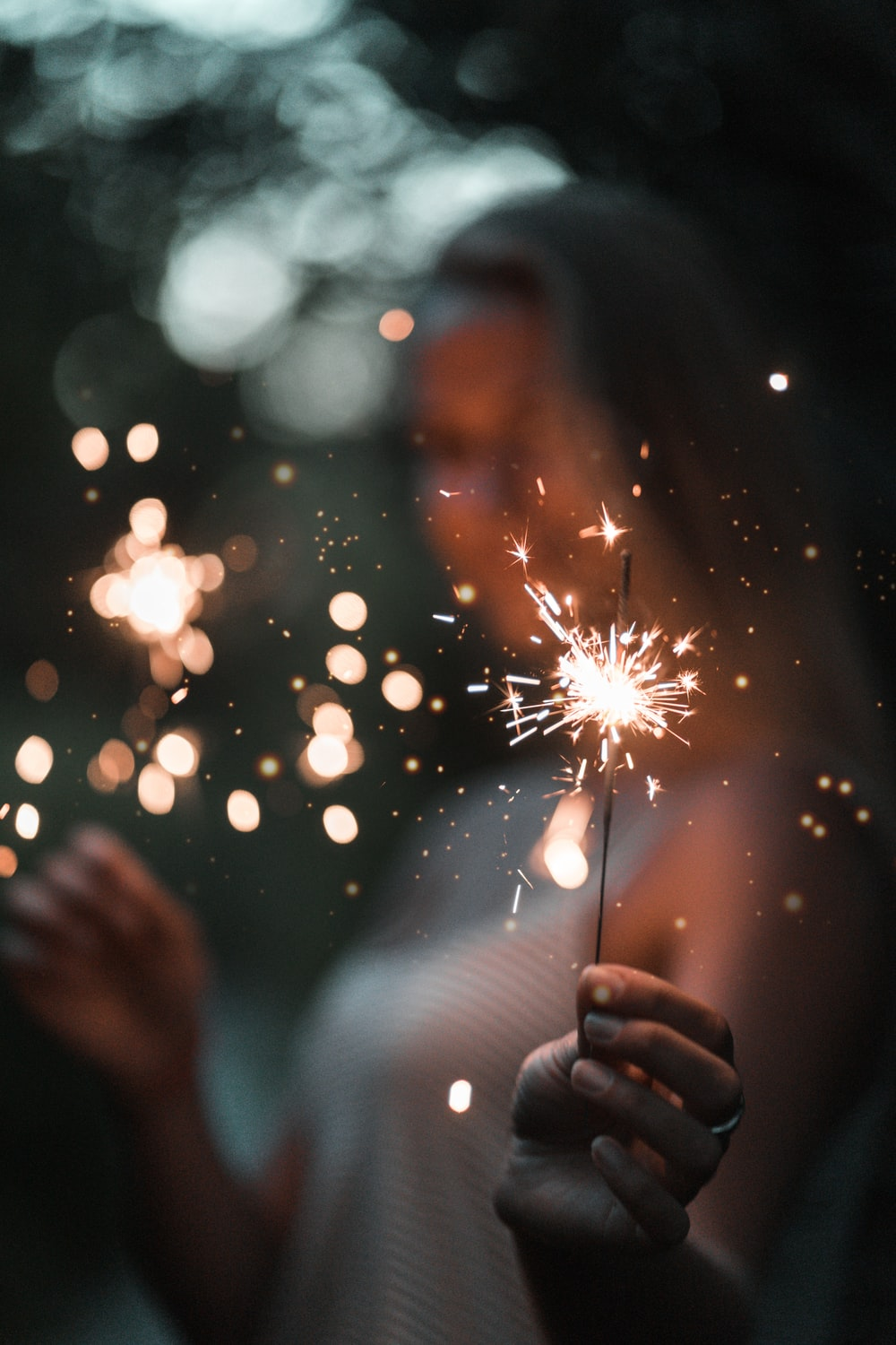 woman holding fire cracker in selective focus photography