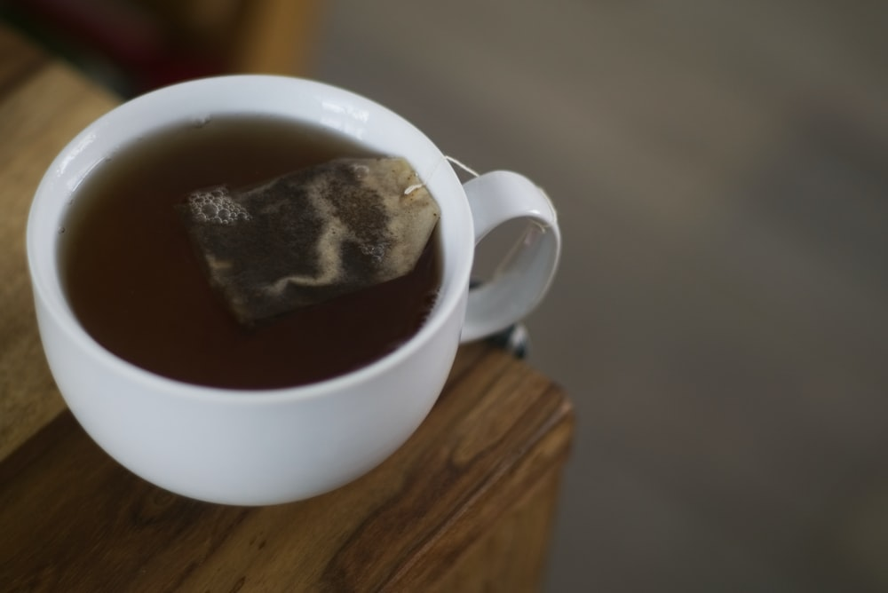 selective focus photography of tea-filled teacup on corner of table