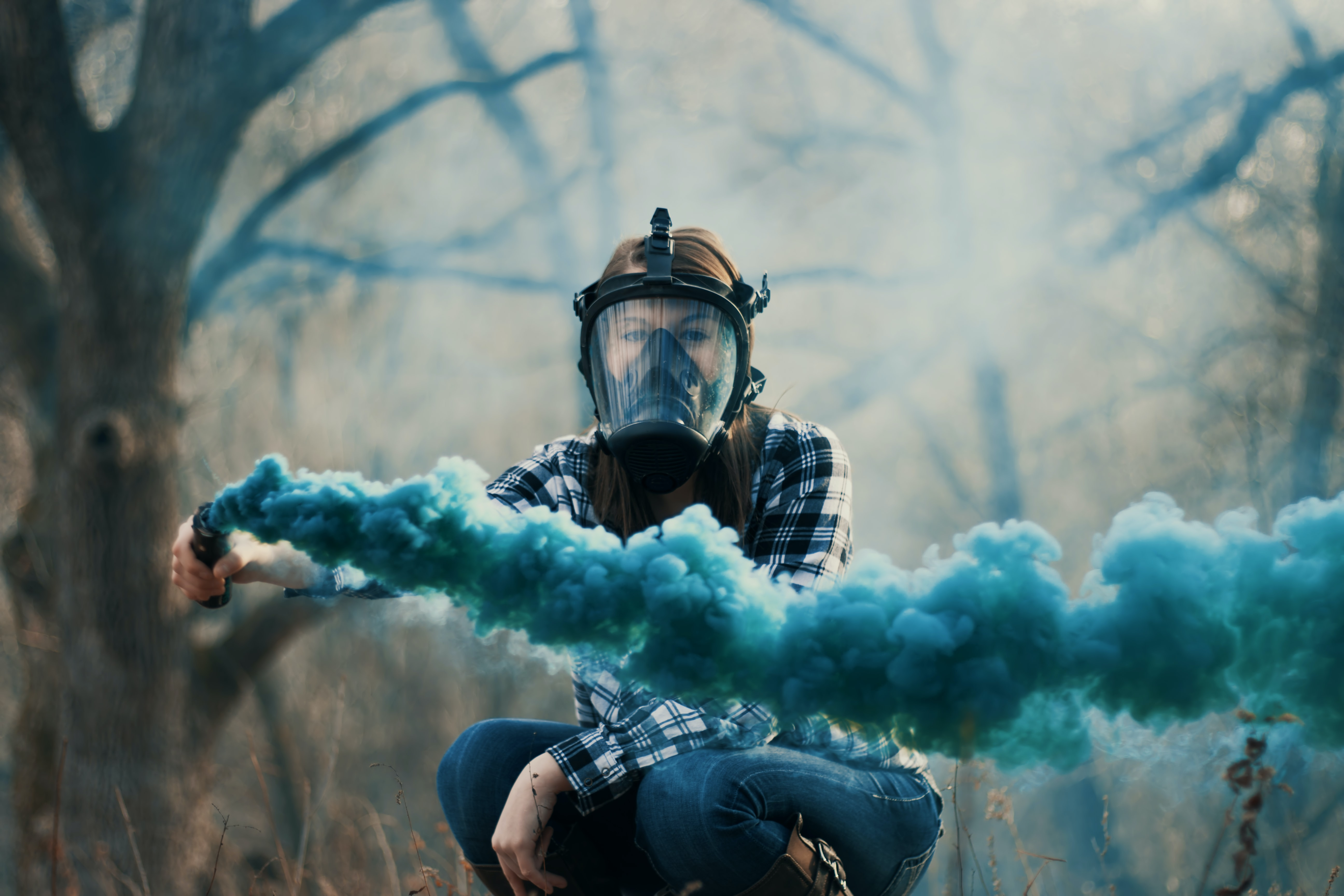 person wearing black gas mask while using blue smoke