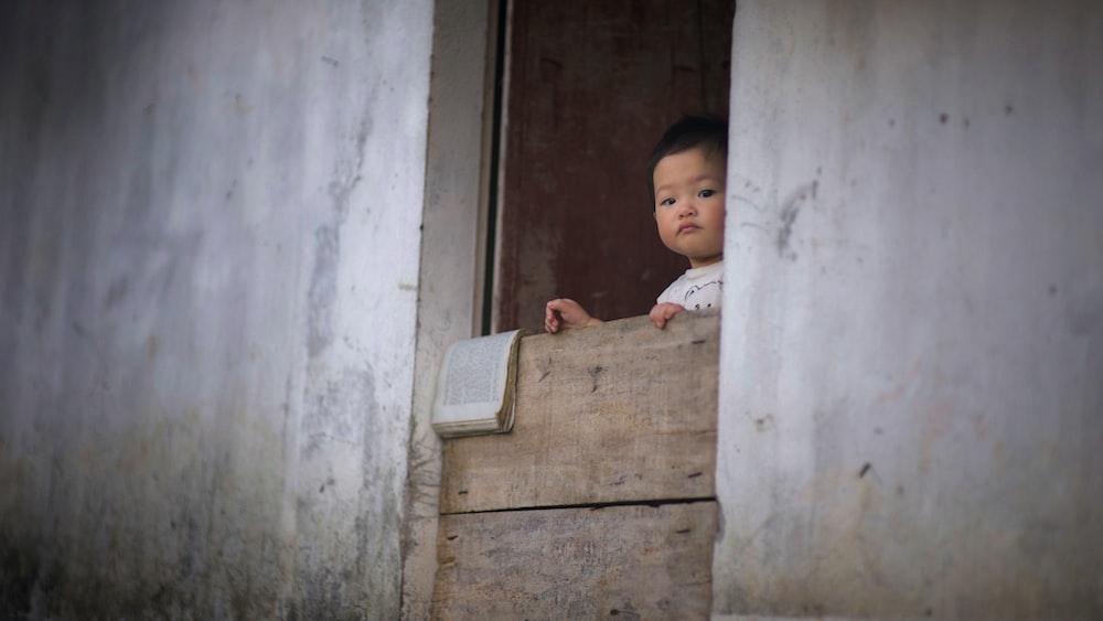 toddler standing near blocked door