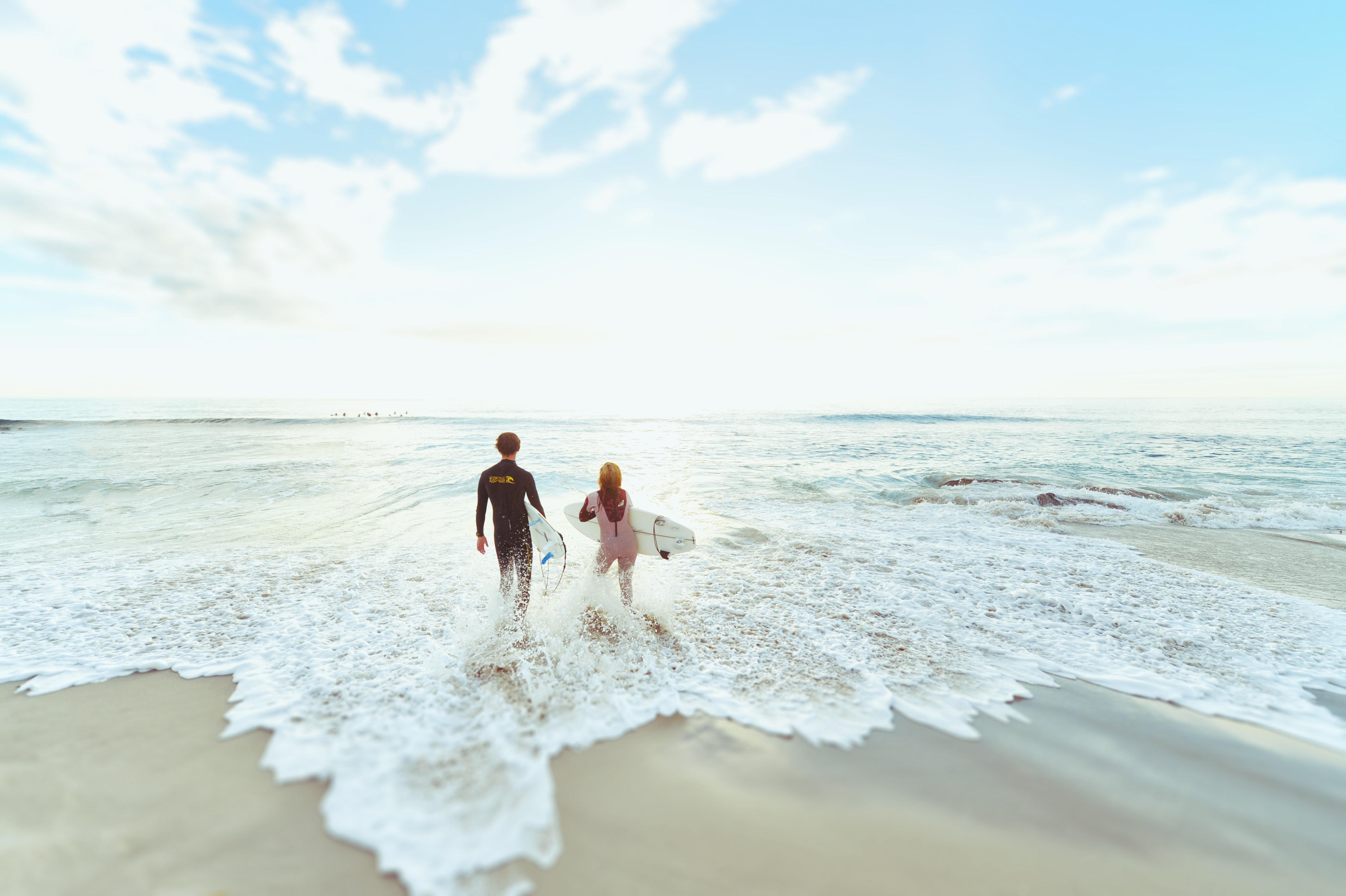 candid photography of man and woman at seashore carrying surfboards under cirrus clouds and blue calm sky
