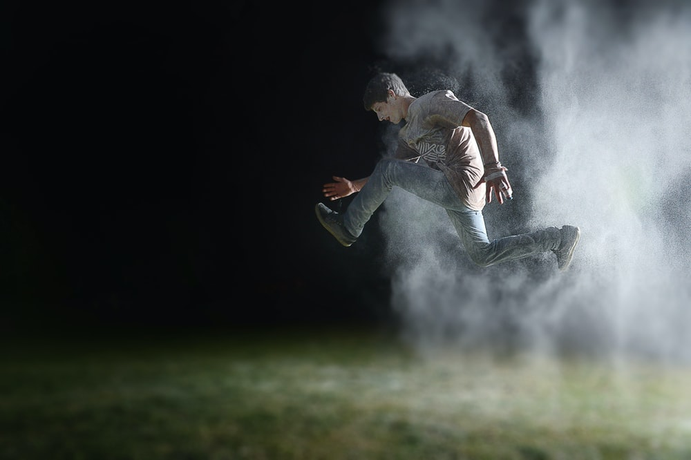 man in gray shirt jumping during night time