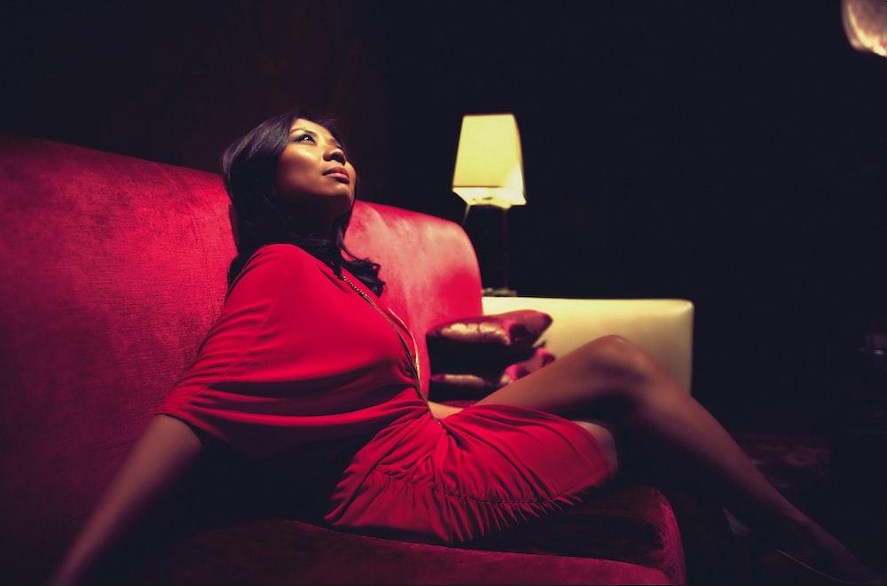 woman sitting on sofa beside desk lamp