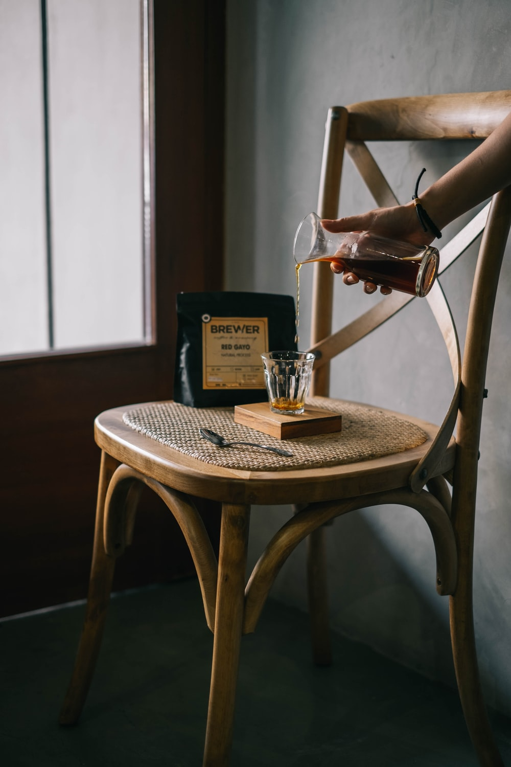 person holding clear glass decanter pouring a whiskey to a clear drinking glass cup on brown wooden chair near clear glass window in room