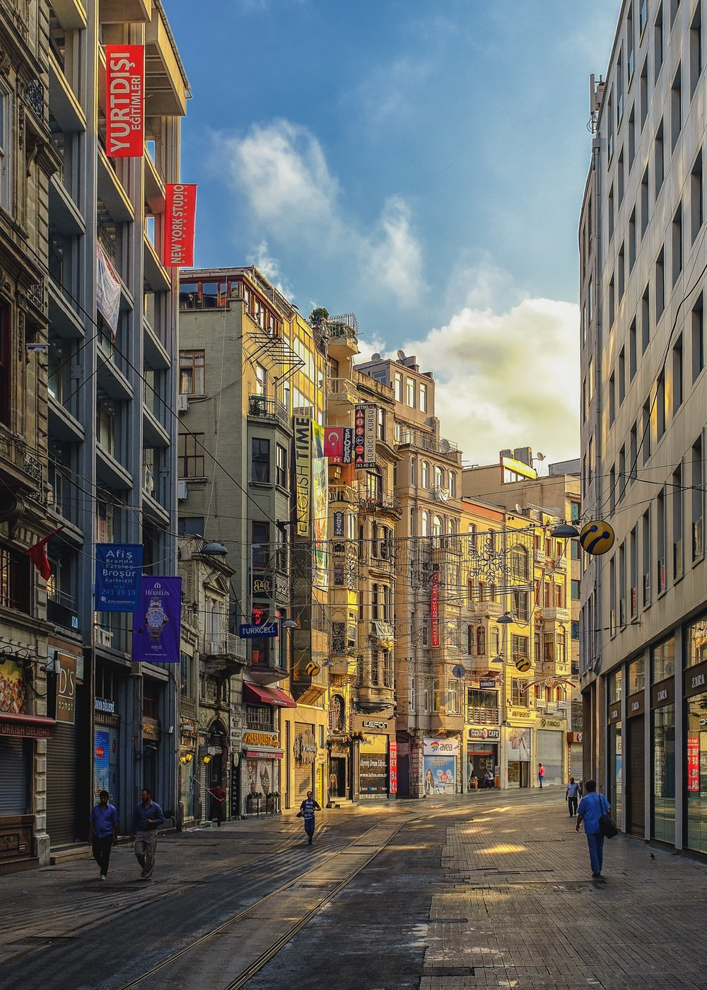 people walking on alley surrounded with buildings artwork