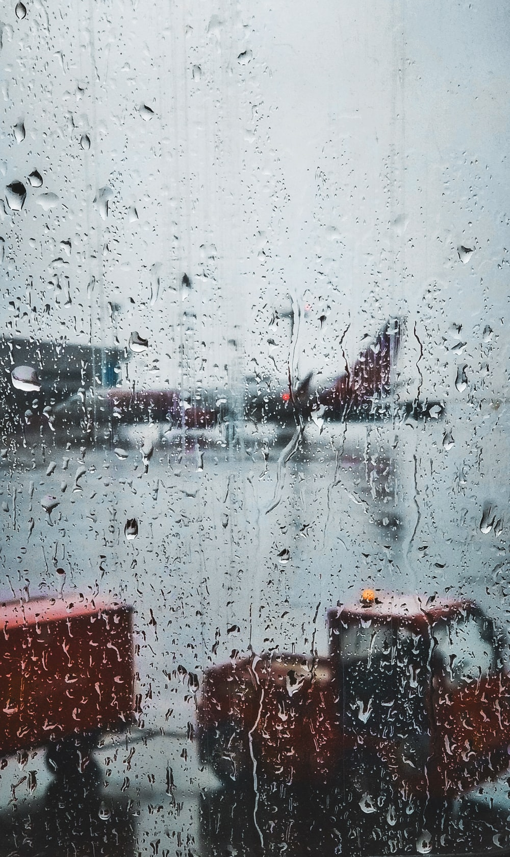 selective focus photography of glass panel with raindrops with view of commuter plane